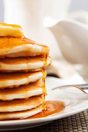 Cropped view of tall stack of dollar pancakes with maple syrup dripping