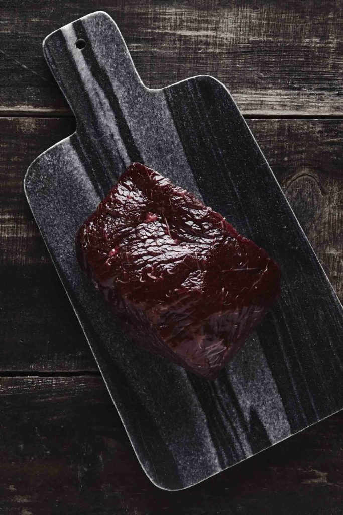 Top view of luxury raw piece of whale meat steak on black marble stone cutting desk and aged vintage wooden table