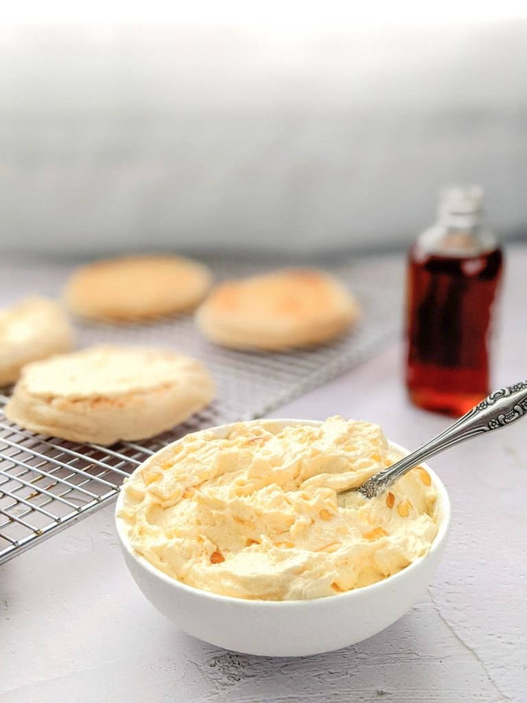 Whipped butter flavoured with maple in a small white bowl on a white table with crumpets in the background.
