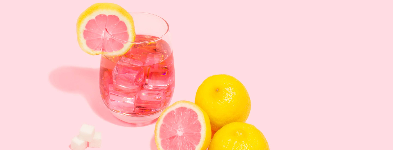 pink grapefruits alongside pink cocktail drink