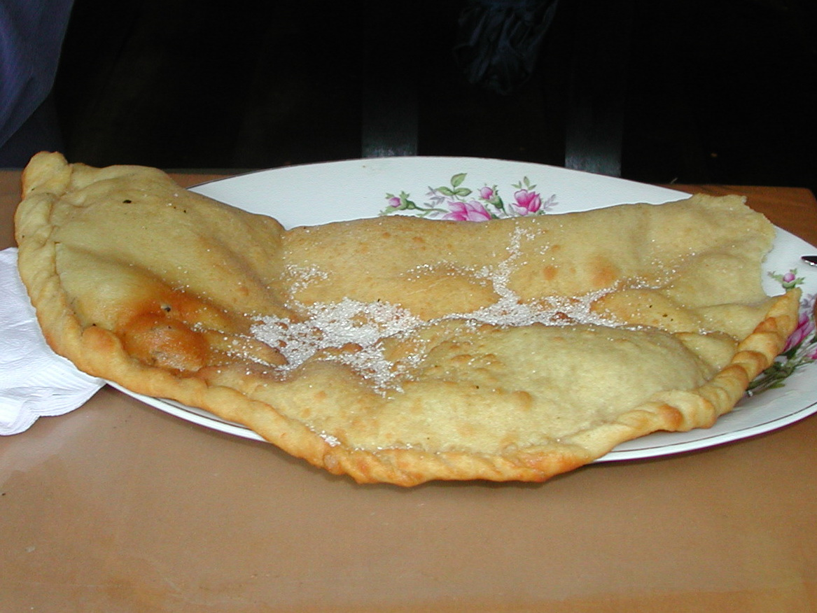Ecuadorian sweet empanada on a plate with sugar