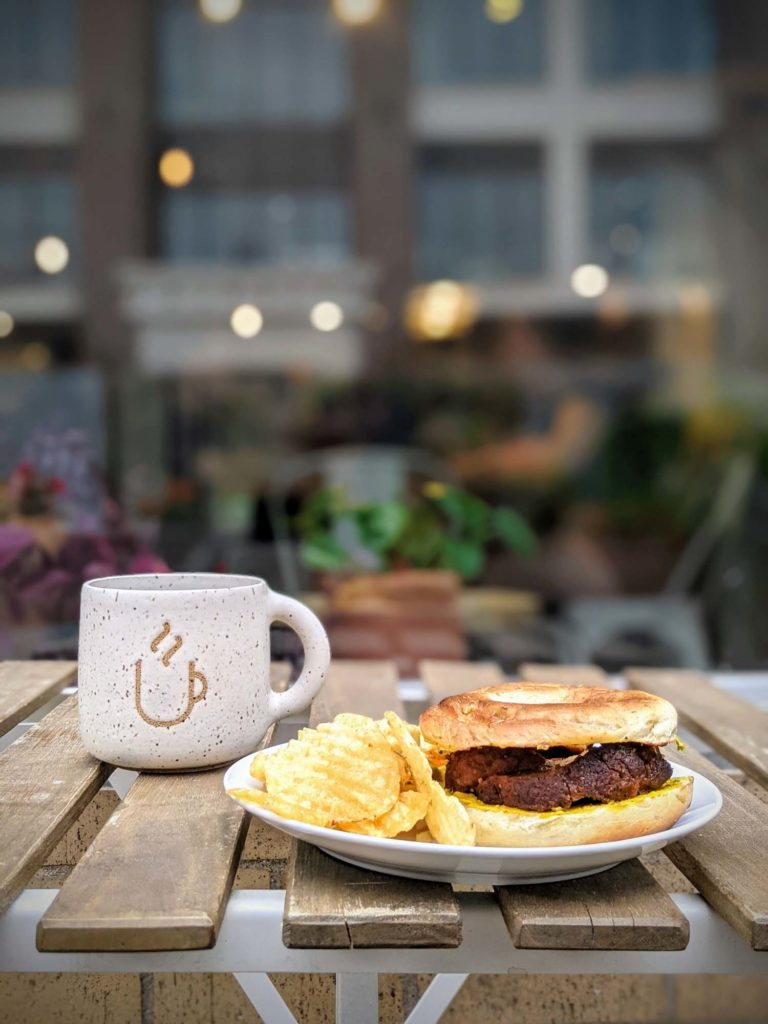 Fredericton Restaurants The Tipsy Muse Impastrami vegan pastrami on rosemary sea salt bagel on table with coffee on patio