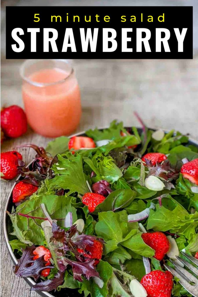 Strawberry salad with spinach, spring mix, arugula, red onion, slivered almonds on a black plate and rustic surface.