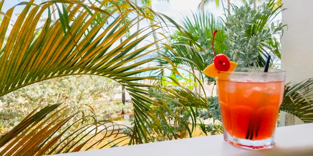 Rum punch on a table with palm trees in back in Barbados