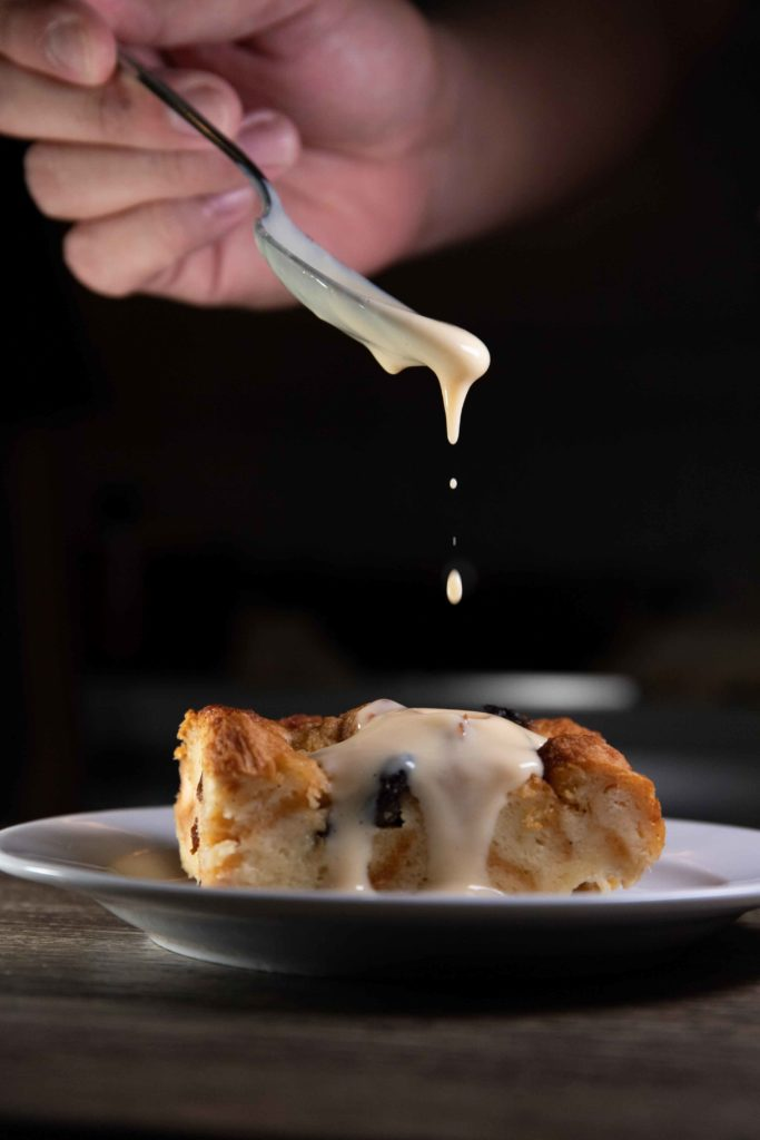 Budin is a common dessert in Costa Rica known as bread pudding, it is on a white plate with a hand adding a sweet topping