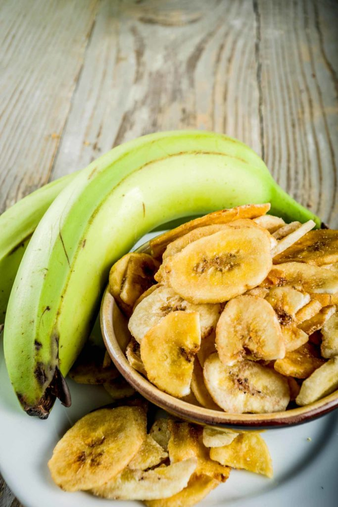 Dried bananas plantains with fresh bananas, wooden background copy space